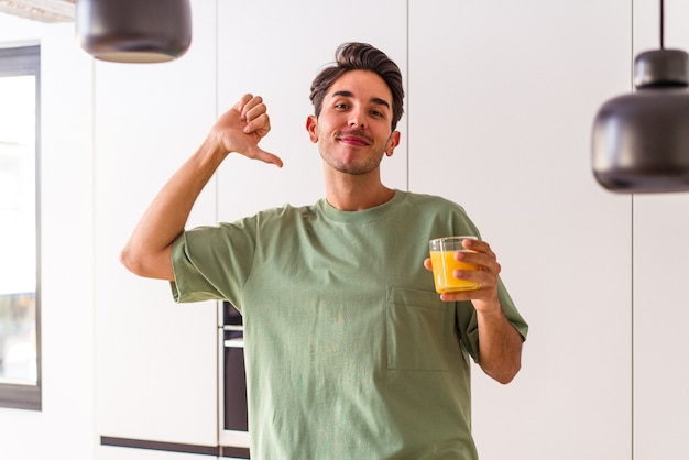 Young mixed race man drinking orange juice in his kitchen feels proud and self confident, example to follow.