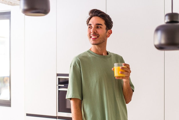 Young mixed race man drinking orange juice in his kitchen looks aside smiling, cheerful and pleasant.