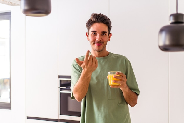 Young mixed race man drinking orange juice in his kitchen pointing with finger at you as if inviting come closer.