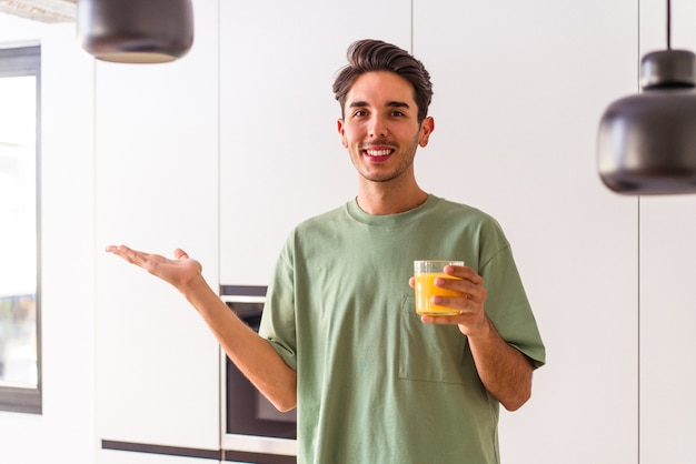 Young mixed race man drinking orange juice in his kitchen showing a copy space on a palm and holding another hand on waist.