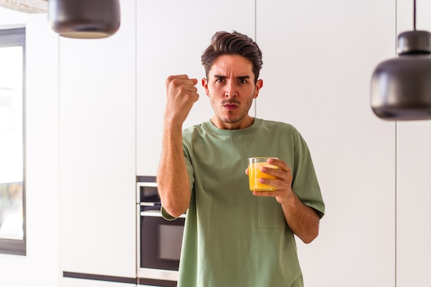 Young mixed race man drinking orange juice in his kitchen showing fist to camera, aggressive facial expression.