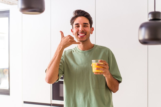 Young mixed race man drinking orange juice in his kitchen showing a mobile phone call gesture with fingers.