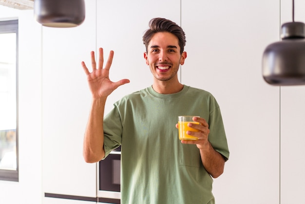Young mixed race man drinking orange juice in his kitchen smiling cheerful showing number five with fingers.
