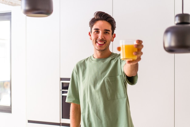 Young mixed race man drinking orange juice in his kitchen