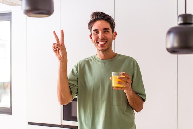 彼の台所でオレンジジュースを飲んでいる若い混血の男は、指で平和のシンボルを示して楽しくてのんきです。