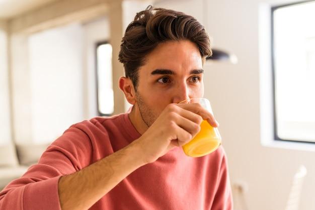 彼の台所でオレンジジュースを飲む若い混血の男