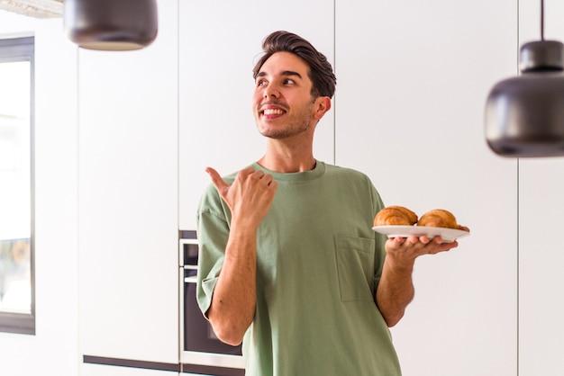 아침에 부엌에서 크루아상을 먹고 있는 젊은 혼혈 남자는 엄지손가락을 치켜들고 웃고 근심 걱정이 없습니다.