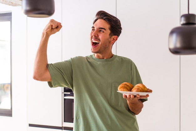 Молодой человек смешанной расы ест круассан на кухне утром, поднимая кулак после победы, концепции победителя.