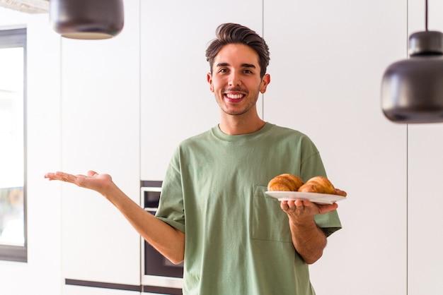 朝、台所でクロワッサンを食べて、手のひらにコピースペースを見せ、腰にもう一方の手を握っている若い混血の男。