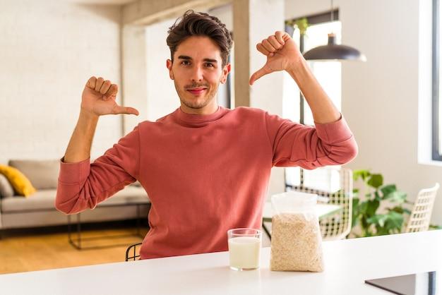 キッチンで朝食にオートミールとミルクを食べる若い混血の男性は、誇りと自信を持っています。