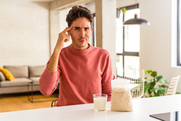 台所で朝食にオートミールとミルクを指で指さし、考え、仕事に集中して食べる若い混血の男。