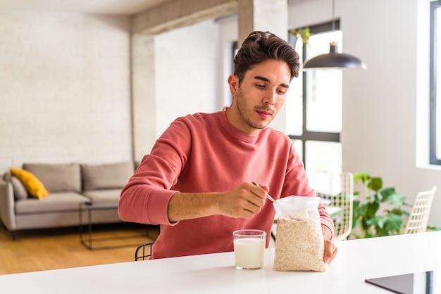 彼の台所で朝食にオートミールとミルクを食べる若い混血の男