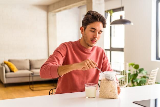 부엌에서 아침으로 오트밀과 우유를 먹는 젊은 혼혈 남자