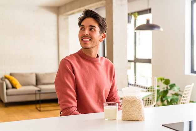 Young mixed race man eating oatmeal and milk for breakfast in his kitchen looks aside smiling, cheerful and pleasant.