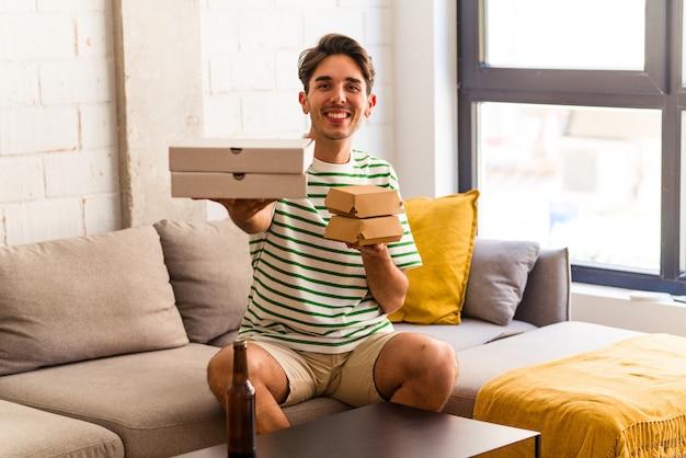ピザとハンバーガーを食べてビールを飲む若い混血の男