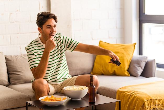ソファに座ってポップコーンを食べる若い混血男