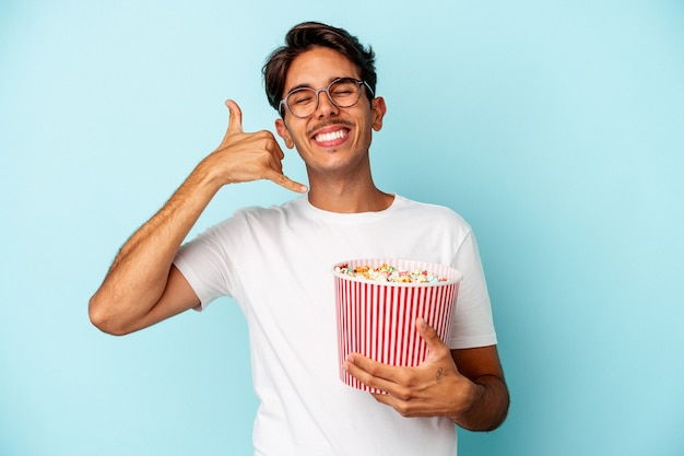 Young mixed race man eating popcorns isolated on blue background showing a mobile phone call gesture with fingers.