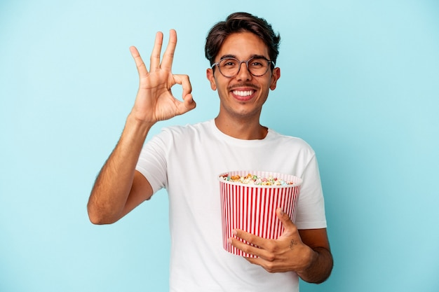 파란색 배경에 격리된 팝콘을 먹고 있는 젊은 혼혈 남자는 확인 제스처를 보여주며 쾌활하고 자신감이 있습니다.