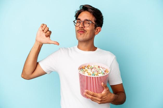 파란색 배경에 격리된 팝콘을 먹는 젊은 혼혈 남성은 따라야 할 본보기인 자부심과 자신감을 느낍니다.