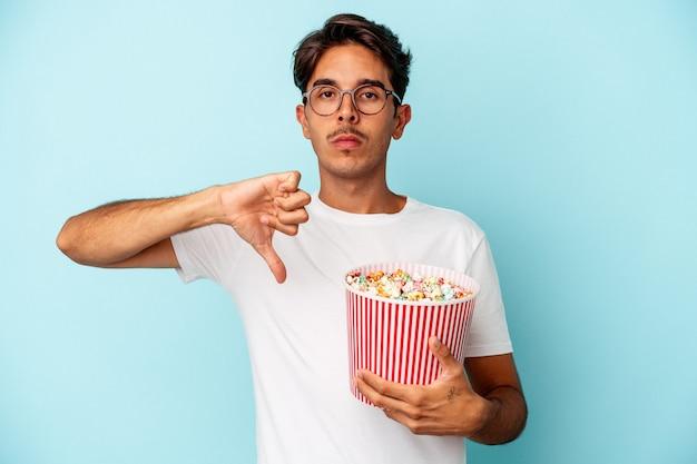파란색 배경에 격리된 팝콘을 먹는 혼혈 청년은 싫어한다는 제스처를 보이고 엄지손가락을 아래로 내립니다. 불일치 개념입니다.