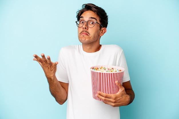 파란색 배경에 격리된 팝콘을 먹고 있는 젊은 혼혈 남자는 어깨를 으쓱하고 혼란스러운 눈을 뜨고 있습니다.
