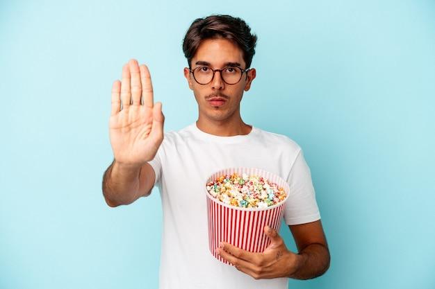 파란색 배경에 격리된 팝콘을 먹고 있는 젊은 혼혈 남성이 정지 신호를 보여주며 손을 뻗은 채 서 있습니다.