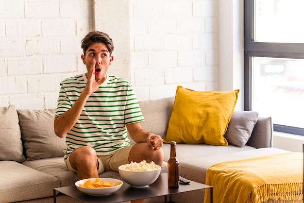 ソファに座ってポップコーンを食べる若い混血の男は、秘密のホットブレーキのニュースを言って脇を見ています