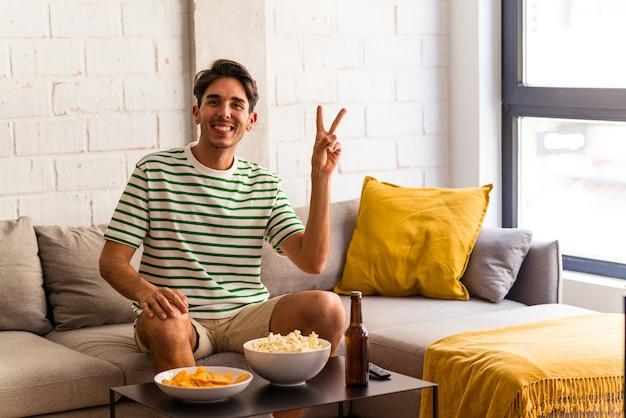 指で平和のシンボルを示して楽しくてのんきなソファに座ってポップコーンを食べる若い混血の男。