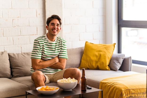 ソファに座って笑って楽しんでポップコーンを食べる若い混血の男。