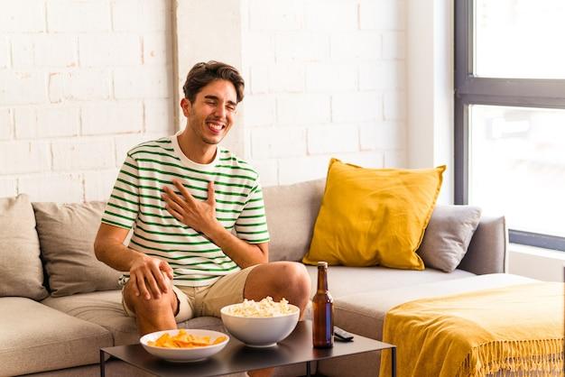 ソファに座ってポップコーンを食べる若い混血の男は、胸に手を置いて大声で笑います。