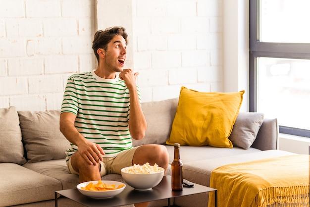 ソファに座って親指の指を離して、笑いながらのんきなポップコーンを食べる若い混血の男。