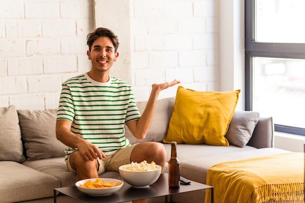 Молодой человек смешанной расы ест попкорн, сидя на диване, показывая место для копии на ладони и держа другую руку на талии.