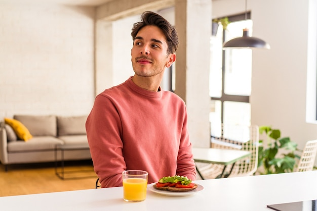 Young mixed race man having breakfast in his kitchen looks aside smiling, cheerful and pleasant.