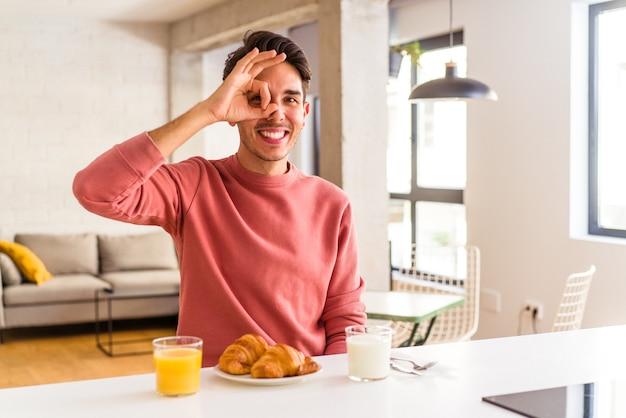 Молодой человек смешанной расы, завтракающий на кухне утром, взволнован, держа на глазах хорошо жест.
