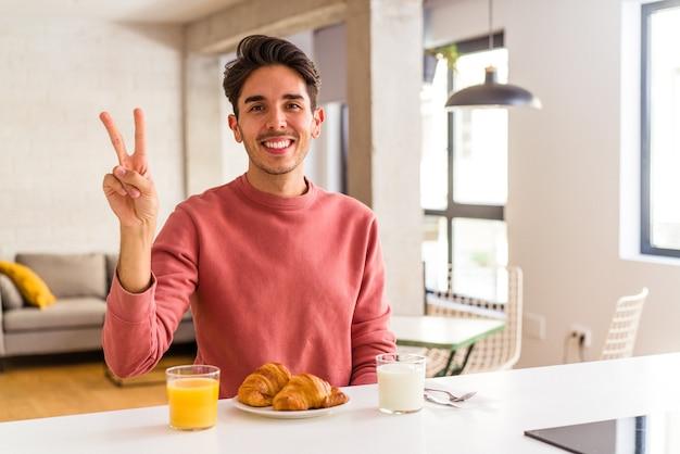 Молодой человек смешанной расы завтракает на кухне утром радостным и беззаботным, показывая пальцами символ мира.