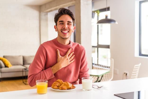 Молодой человек смешанной расы завтракает на кухне утром, громко смеясь, держа руку на груди.