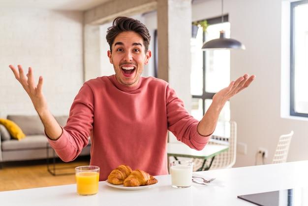 朝、キッチンで朝食をとる若い混血の男は、嬉しい驚きを受け取り、興奮し、手を上げます。