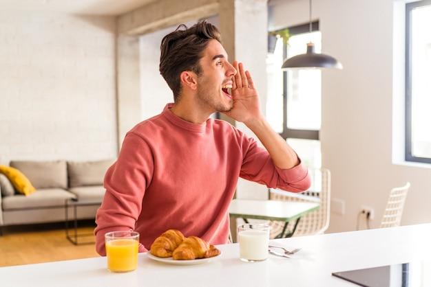 Молодой человек смешанной расы завтракает на кухне утром, кричит и держит ладонь возле открытого рта.