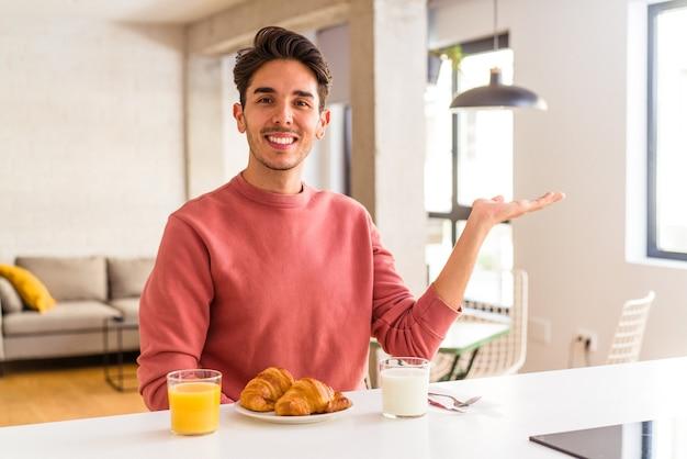 Молодой человек смешанной расы завтракает на кухне утром, показывая место для копии на ладони и держа другую руку на талии.