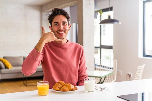 Молодой человек смешанной расы завтракает на кухне утром, показывая жест мобильного телефона пальцами.