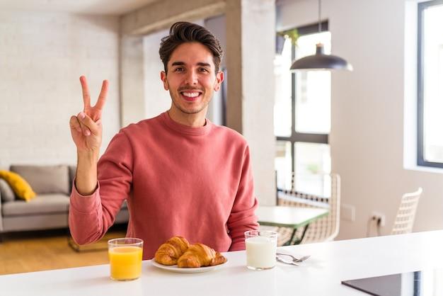 朝、キッチンで朝食をとっている若い混血の男が指で2番目を示しています。