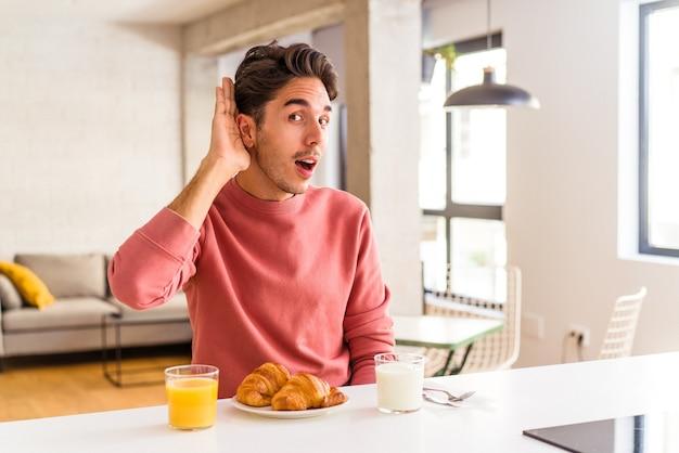 ゴシップを聞いて朝、キッチンで朝食をとっている若い混血の男。
