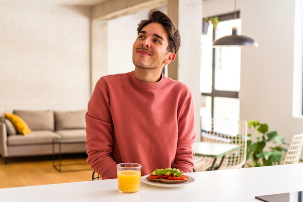 目標と目的を達成することを夢見て彼の台所で朝食をとっている若い混血の男
