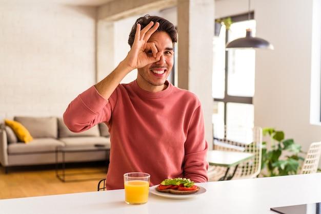 彼の台所で朝食をとっている若い混血の男は、目で大丈夫なジェスチャーを保ちながら興奮していました。