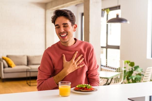 台所で朝食をとっている若い混血の男は、胸に手を置いて大声で笑います。