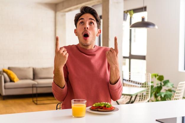 Молодой человек смешанной расы завтракает на кухне, указывая вверх с открытым ртом.