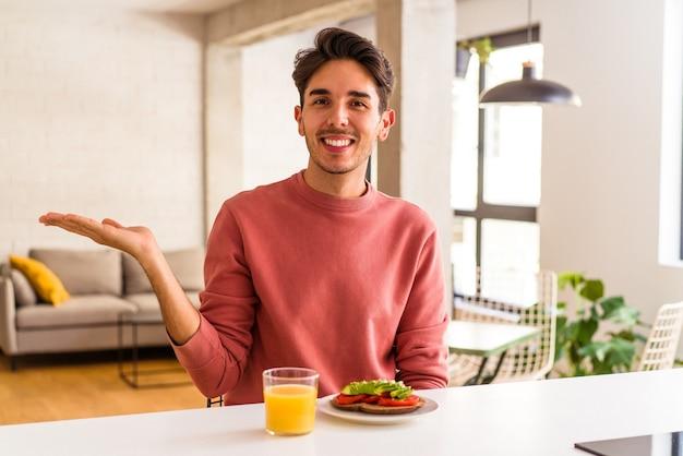 手のひらにコピースペースを示し、腰に別の手を持って彼の台所で朝食をとっている若い混血の男。