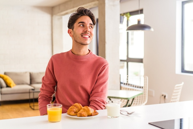 Young mixed race man having breakfast in a kitchen on the morning looks aside smiling, cheerful and pleasant.