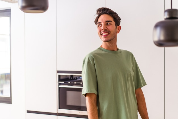 Young mixed race man in his kitchen looks aside smiling, cheerful and pleasant.