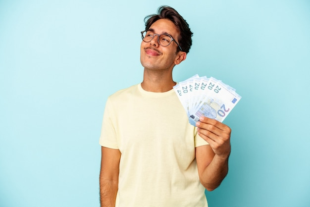 Young mixed race man holding bills isolated on blue background dreaming of achieving goals and purposes